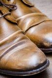 Chaussures en cuir de Brown sur un plancher en bois Photographie stock libre de droits