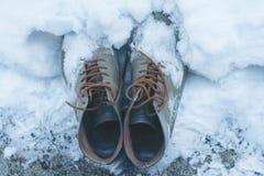 Chaussures en cuir de vintage couvertes dans la neige Image libre de droits