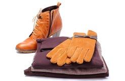 Chaussures en cuir féminines, gants et vêtements sur le fond blanc Image libre de droits
