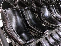Chaussures en cuir noires brillantes du ` s d'hommes sur l'étagère Photo stock