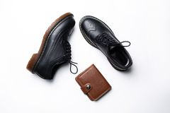 Chaussures en cuir noires de Derby avec des semelles de polyur?thane et une bourse brune avec un bouton sur un fond blanc images libres de droits