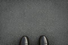 Chaussures en cuir noires sur la route goudronnée Photos libres de droits