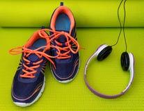 Chaussures et écouteurs lumineux sur le tapis roulé de yoga Photographie stock