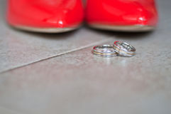 Chaussures et anneaux de mariage rouges Photographie stock libre de droits