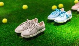 Chaussures et balles de tennis de sport sur une herbe Photographie stock