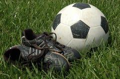 Chaussures et bille du football dans l'herbe Image libre de droits