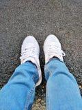 Chaussures et blues-jean de toile blanches photographie stock