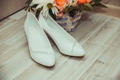 Chaussures et bouquet blancs de mariage de jeune mariée dans le panier Images stock