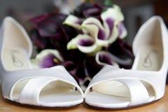 Chaussures et bouquet du haut talon de la mariée Photo stock
