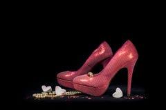 Chaussures et coeurs roses de partie sur le fond noir Photographie stock