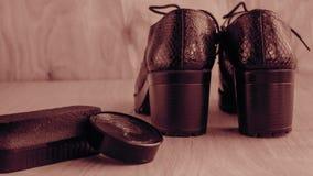 Chaussures et crème de récurage sur le plancher Nettoyez les chaussures pour la marche photographie stock