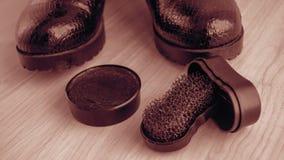 Chaussures et crème de récurage sur le plancher Nettoyez les chaussures pour la marche photographie stock libre de droits