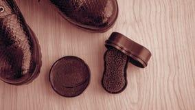 Chaussures et crème de récurage sur le plancher Nettoyez les chaussures pour la marche images stock