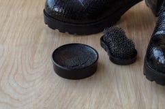 Chaussures et crème de récurage sur le plancher Nettoyez les chaussures pour la marche photos stock
