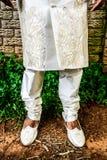 Chaussures et jambes d'un marié asiatique dans un marié indien traditionnel blanc photos stock