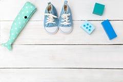 Chaussures et jouets de bleus layette sur un fond en bois blanc Vue de Photos stock