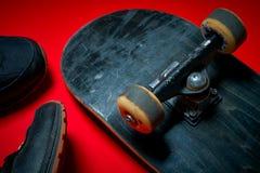 Chaussures et planche à roulettes utilisée sur un fond rouge Images libres de droits