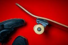 Chaussures et planche à roulettes utilisée sur un fond rouge Images stock