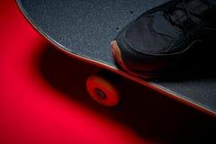 Chaussures et planche à roulettes utilisée sur un fond rouge Photo libre de droits