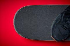 Chaussures et planche à roulettes utilisée sur un fond rouge Photos libres de droits