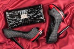 Chaussures et sac se trouvant sur le tissu rouge Photos stock
