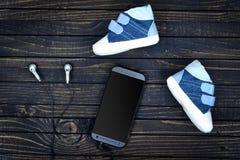 Chaussures et téléphone d'enfant sur le plancher Photo stock