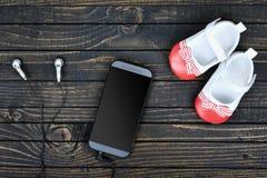 Chaussures et téléphone d'enfant sur le plancher Image stock