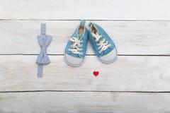 Chaussures et un papillon-lien pour le garçon sur un fond en bois La Floride Images libres de droits
