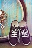 Chaussures et une roue de bicyclette sur un fond de barrière en bois bleue Photographie stock libre de droits