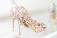 Chaussures femelles de beau talon haut d'or de scintillement sur l'étagère en verre Accessoires de mariage Chaussures de Cendrill Photos stock