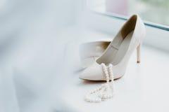Chaussures femelles enes ivoire de mariage avec des perles juweliry sur la fenêtre Images stock