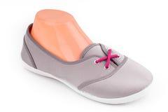 Chaussures grises bon marché de sport avec les dentelles rouges pour la femme Photographie stock libre de droits