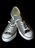 Chaussures grises de la jeunesse d'espadrilles au fond noir Photographie stock libre de droits