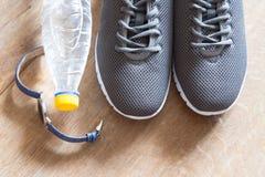 Chaussures grises de sport avec le chronomètre et la bouteille de waterr Paires o Photos stock