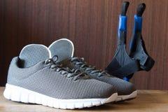 Chaussures grises de sport avec les cannes nordiques et l'inso orthopédique Photos stock