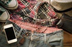 Chaussures intelligentes accessoires de jeans de téléphone, portefeuille, jeans, chemise de chapeaux sur un plancher en bois pour Photo stock