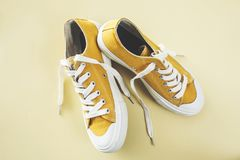 Chaussures jaunes de sport sur le fond jaune Photographie stock