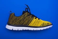 Chaussures jaunes et noires de femme de sport d'isolement sur le fond bleu Photos libres de droits