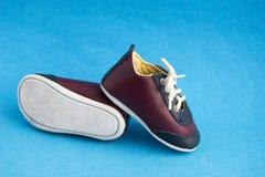 Chaussures mignonnes de sport pour le petit garçon d'isolement sur le fond bleu Petites espadrilles de bébé Image stock