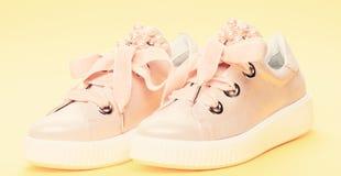 Chaussures mignonnes sur le fond jaune Les chaussures pour des filles ou des femmes décorées de la perle perlent Paires de pâle - image stock