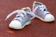 Petites chaussures de bébé au sol Photos libres de droits