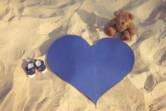 Chaussures minuscules, ours de nounours et un coeur Images libres de droits