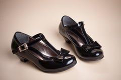 Chaussures noires de fille de cuir d'éclat avec le ruban noir Images stock