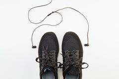 Chaussures noires de sport avec l'écouteur sur le fond blanc Photos stock