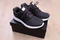 Chaussures noires de sport avec la boîte sur le fond en bois Photographie stock libre de droits