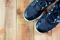 Chaussures noires de sport sur en bois Photographie stock libre de droits