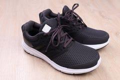 Chaussures noires de sport sur le fond en bois Image libre de droits