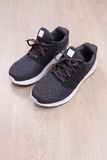 Chaussures noires de sport sur le fond en bois Images stock