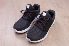 Chaussures noires de sport sur le fond en bois Photos libres de droits