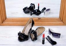 Chaussures noires de talon avec les verres et le rouge à lèvres photographie stock libre de droits